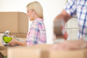 Women packing some household things in moving boxes