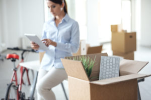 Business woman moving in a new office, she is using a digital tablet, selective focus, open cardboard box on foreground