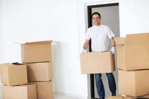Smiling man carries a box