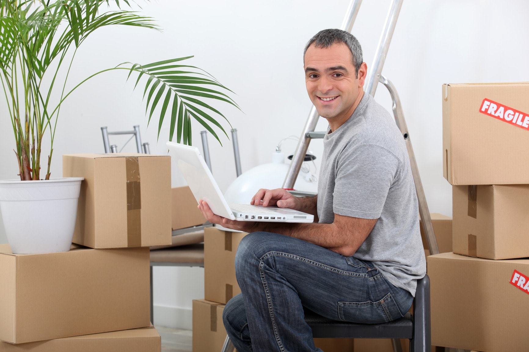 Man using a laptop computer sitting amongst cardboard boxes